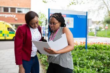 Two women stood talking outside a hospital