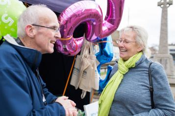 Elderly man and woman talking together at a Healthwatch event