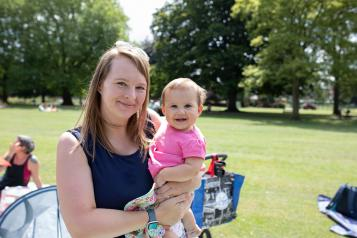 A woman in a park holding a young child