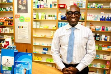 Ade Williams, a man, standing behind a counter in a pharmacy