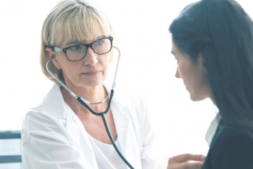 A doctor with a stethoscope listening to a patient's chest