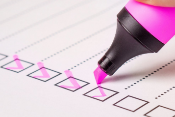 A pink highlighter being used to tick boxes on a list
