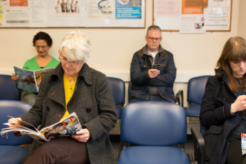 Four people sitting on blue chairs in a waiting room
