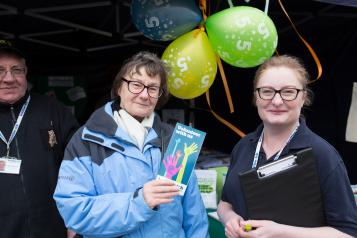 A Healthwatch employee at a community event and a member of the public holding a leaflet