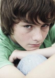 A young boy sitting down hugging his knees